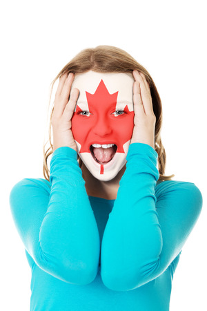 Woman with Canada flag painted on face. photo