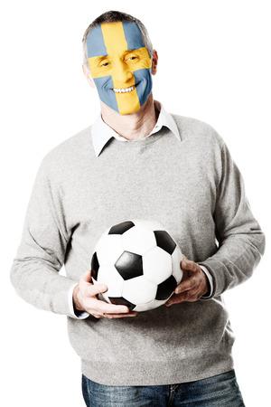 bandera suecia: Hombre maduro con Suecia bandera pintada en la cara.