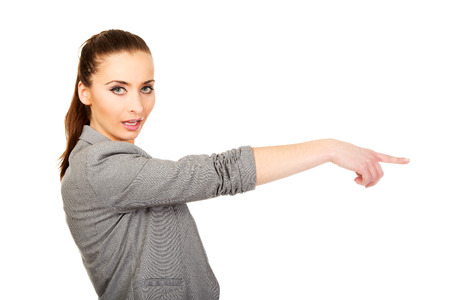 aside: Beautiful confident businesswoman pointing aside. Stock Photo