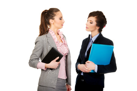 eachother: Two businesswomans with their notes.