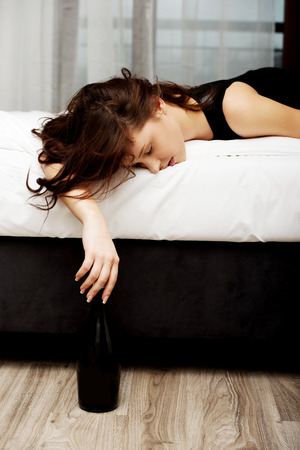 drunk woman: Drunk woman sleeping on bed with bottle of wine.