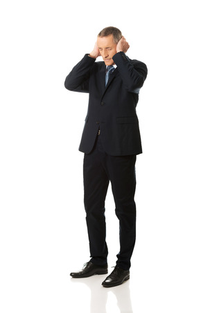 hands covering ears: Tired mature businessman covering ears with hands.