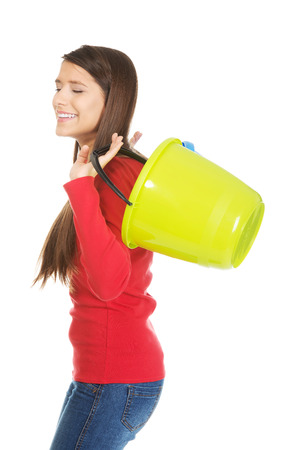 drudgery: Woman holding empty colorful plastic buckets.