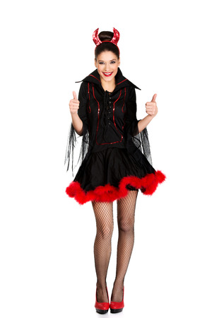 Beautiful woman in devil carnival costume with thumbs up. photo