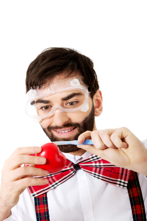 Determined man wearing suspenders cutting heart model with scalpel.. photo