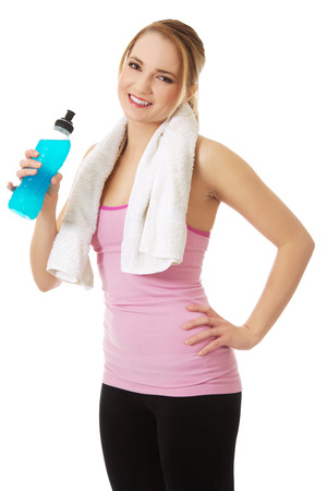 isotonic: Attractive woman in fitness clothes drinking isotonic drink.