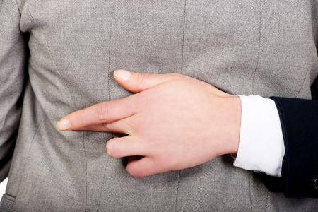 Businesswoman fake fingers crossed while embracing. photo