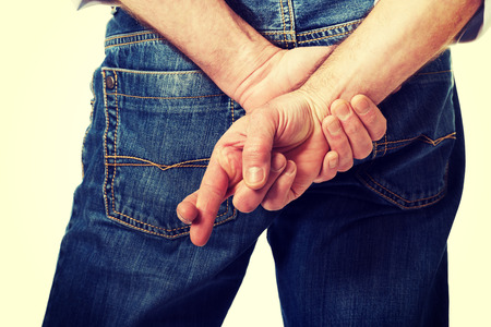 crossed fingers: Male hands with crossed fingers. Stock Photo