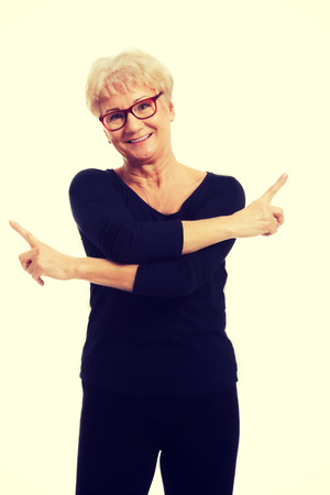 both sides: Happy senior woman pointing on both sides Stock Photo