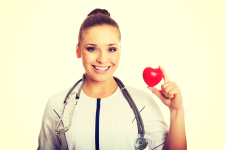 Smiling female doctor holding heart model. photo