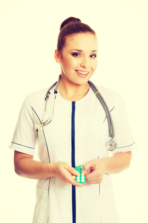 doctor holding pills: Happy female doctor holding pills. Stock Photo
