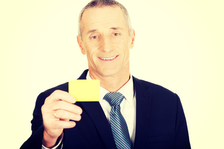 cardkey: Mature businessman showing a yellow identity name card. Stock Photo