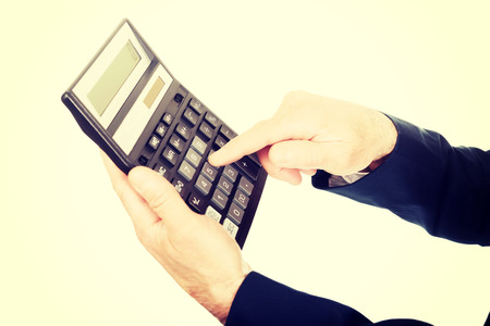 empujando: Financiers dedo presionando el botón en la calculadora.