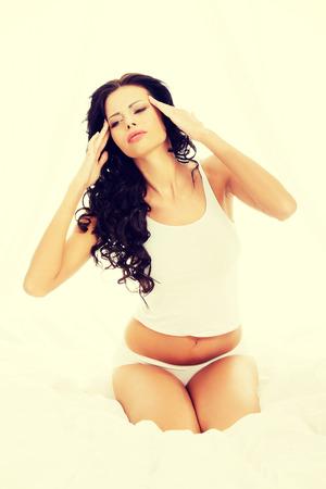 pyjama: Woman with headache sitting on her bed.