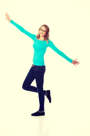 wide open: Cheerful teenage woman with arms wide open