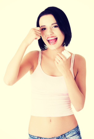 flossing: Young caucasian woman flossing her teeth.