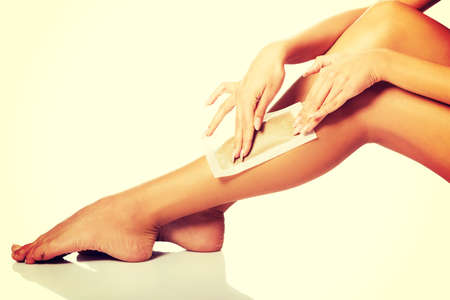 waxed legs: Spa woman waxing her leg Stock Photo