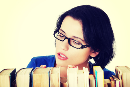 woman searching: Young woman searching for an interesting book. Stock Photo