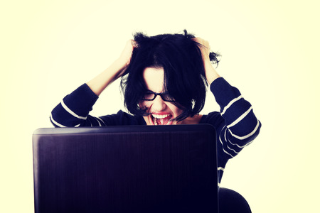 e waste: Angry student woman with a laptop.