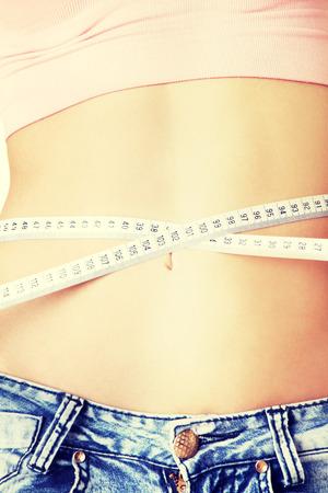 Slim woman measuring her waistline photo