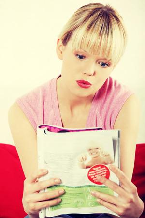 Pretty blonde woman reading a newspaper.