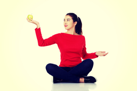 crosslegged: Woman sitting cross-legged holding an apple.