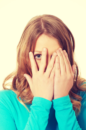 hands covering face: Teenage woman covering her face with hands