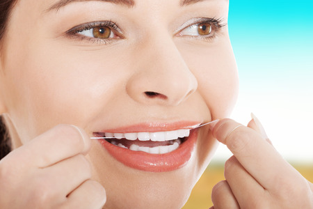 flossing: Happy young woman flossing teeth. Stock Photo