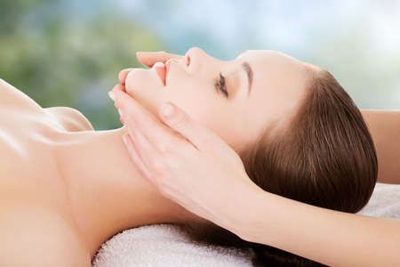 treatments: Woman receving face massage in spa. Stock Photo