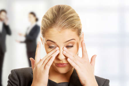 sad eyes: Stressed businesswoman suffering from eyes pain. Stock Photo