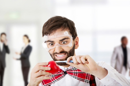 suspenders: Determined man wearing suspenders cutting heart model with scalpel.