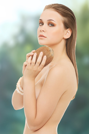 nude women: Attractive spa topless woman with coconut. Stock Photo