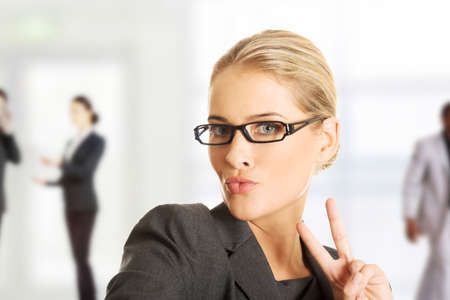 peace sign: Business woman showing victory or peace sign.