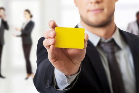 man holding sign: Handsome businessman showing his yellow personal card. Stock Photo