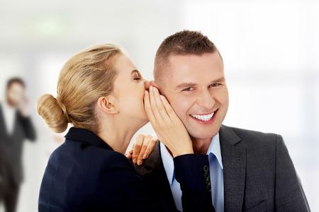 hearsay: Businesswoman whispers gossip to businessman. Stock Photo