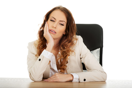 unmotivated: Beautiful exhautsed businesswoman at the desk. Stock Photo