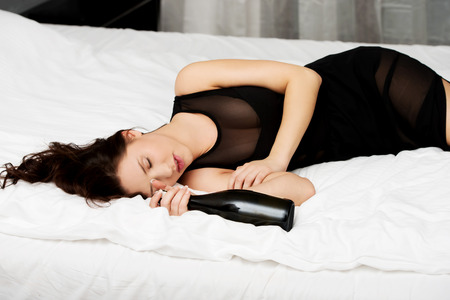borracho: Mujer borracha que duerme en la cama con una botella de vino. Foto de archivo