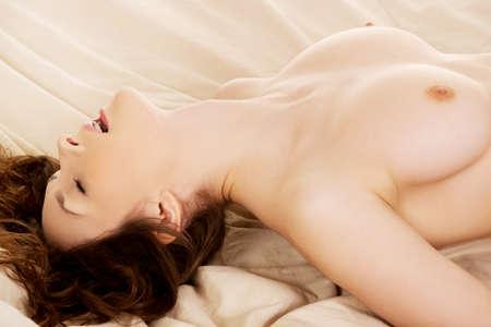 Junge nackte Frau im Bett bekommen Orgasmus.
