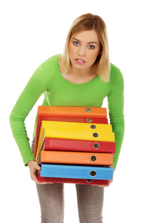binders: Overloaded woman with heavy binders. Stock Photo