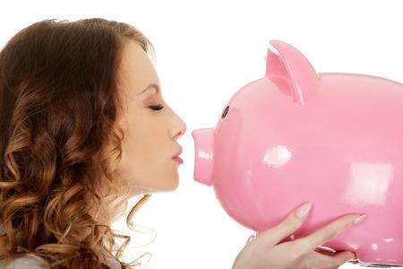 coinbank: Happy business woman kissing a piggybank. Stock Photo