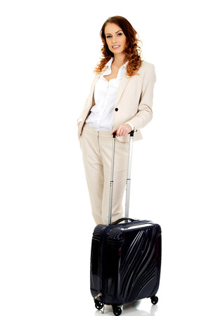 dragging: Businesswoman dragging heavy wheeled suitcase. Stock Photo