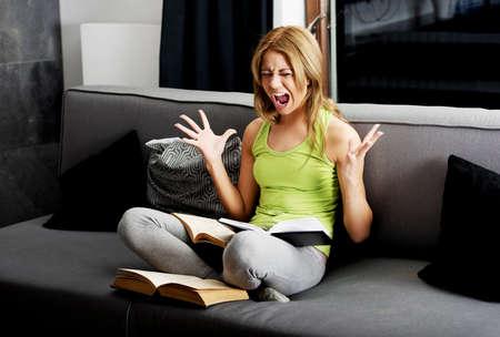 mujer enojada: Joven mujer adolescente enojado aprender a examen en un sofá. Foto de archivo