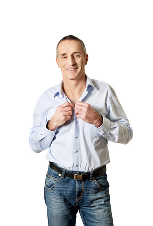 Handsome mature man buttoning his shirt. photo