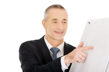 flip chart: Mature businessman presenting something on flip chart. Stock Photo