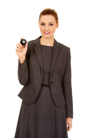 billard: Happy businesswoman holding eight billiard ball.