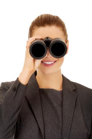 corporate espionage: Caucasian businesswoman looking through binoculars.