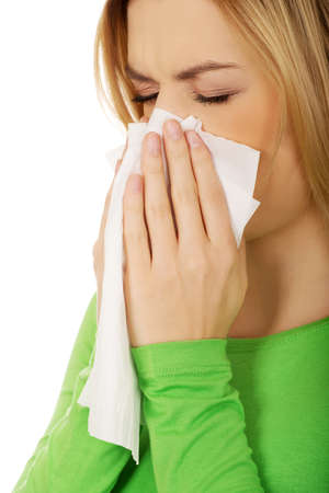 sneezing: Ill woman sneezing to tissue.