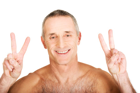 v shape: Happy mature shirtless man with victory sign.