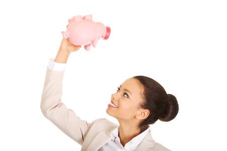 coinbank: African business woman shaking piggybank. Stock Photo