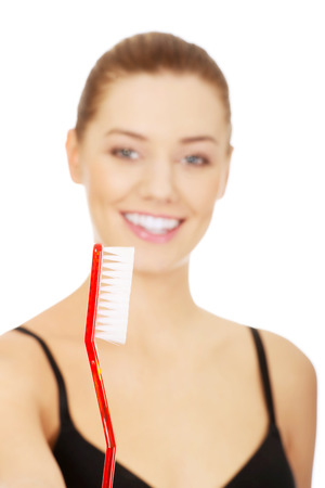oversized: Young woman with oversized toothbrush.